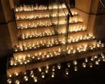 334 lit candles in glass jars on the steps of the Town Hall, at night